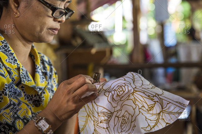 Ubud, Bali, Indonesia - June 7, 2015: An Indonesian woman paints batik by hand in Ubud, Bali
