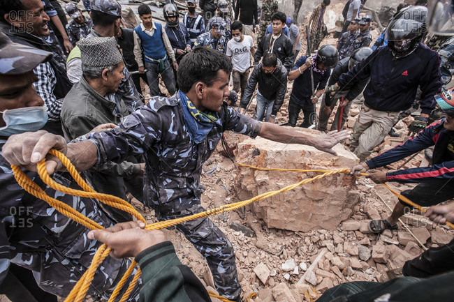 Sundhara, Bagmati, Nepal - April 25, 2015: Rescuers work together  on removing rubble in an effort to recover bodies.