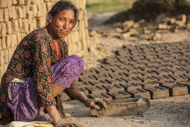 Lele Village, Bagmati, Nepal - May 4, 2015: Making adobe to rebuild houses. Lele Village, 16 Kms from Patan. Nepal. Tears have dried. No time for mourning or waiting for the Aid. Lele people are self-helping to build shelter from the remains for their broken house.