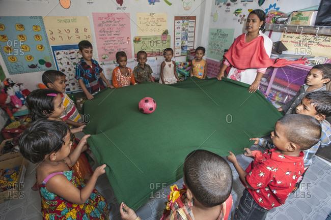Dhaka, Dhaka, Bangladesh - November 17, 2013: Urban Slum kids go to the Pre-school. Dhaka, Bangladesh. Seen here students playing a ball game with teacher.