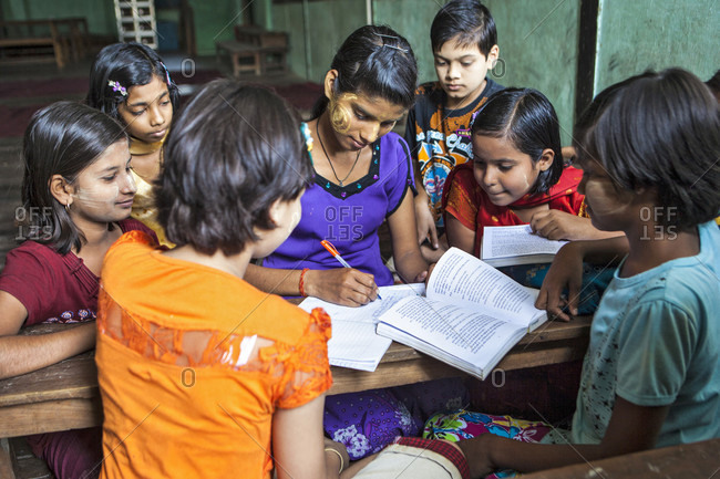 Jiwabari, Jiwabari, Myanmar - April 4, 2015: Class teacher comparing notes for Hindi class students at Arya Gurukul, Arya Samaj Temple, Zyd, that was  established in 20-02-2012. Jiwabari, Myanmar.