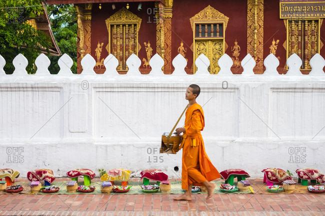 Luang Prabang, Louangphabang, Laos - May 16, 2015: Buddhist novice monks receive alms (Tak Bat) in front of Wat Sene Souk Haram temple, Luang Prabang, Louangphabang Province, Laos