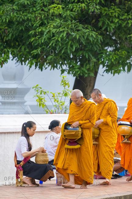 Luang Prabang, Louangphabang, Laos - May 16, 2015: Buddhist novice monks receive alms (Tak Bat) in front of Wat Sirimoungkhoun Sayaram temple, Luang Prabang, Louangphabang Province, Laos