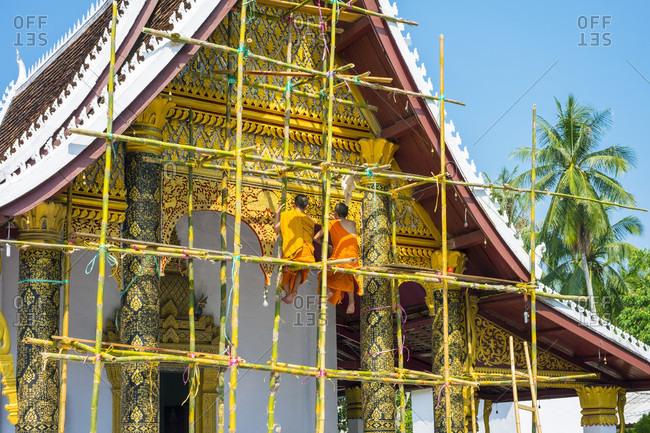 Luang Prabang, Louangphabang, Laos - May 16, 2015: Buddhist novice monks painting temple facade, Wat Sirimoungkhoun Sayaram, Luang Prabang, Louangphabang Province, Laos