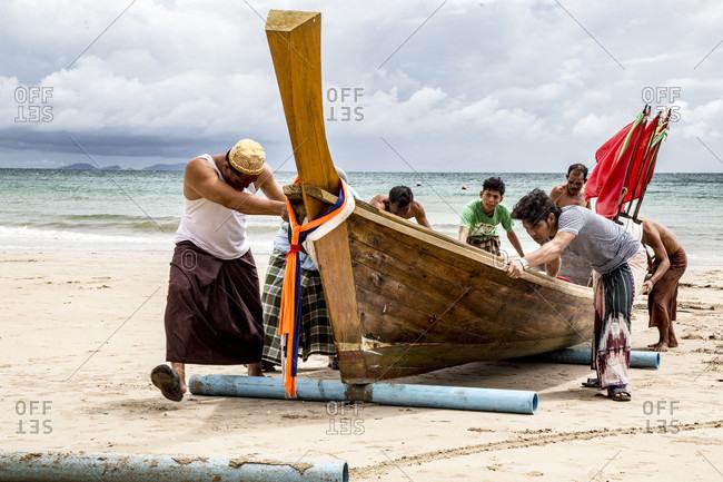 Koh Lanta, Krabi Province, Thailand - October 3, 2014: Fishermen on Koh Lanta Island in Thailand push Boat to Shore