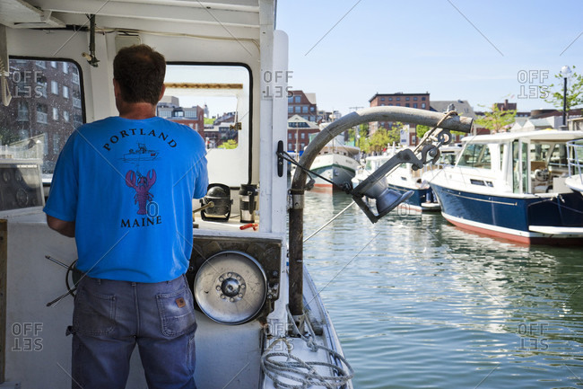 Portland, Maine, United States - June 4, 2015: A boat captain steers his lobster boat into a marina, Portland, Maine
