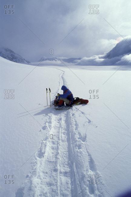 Denali National Park, Alaska, USA - April 15, 1991: USA, Alaska, Denali National Park, (MR) Rudiger Stuiss rests on sled along Kahiltna Glacier while climbing Mt. McKinley