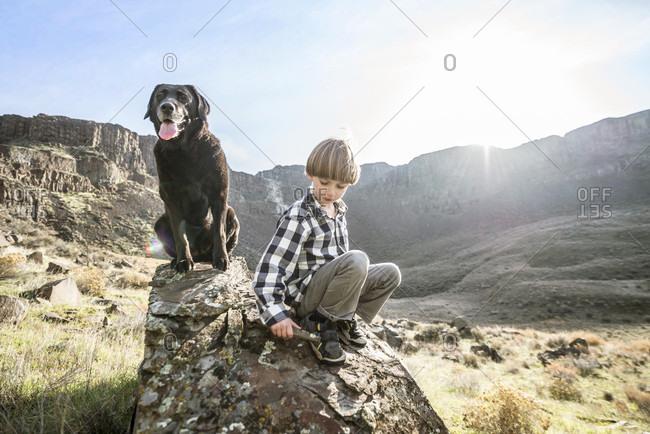 Washington, USA - November 25, 2016: A Boy And His Dog Relaxing On Rock