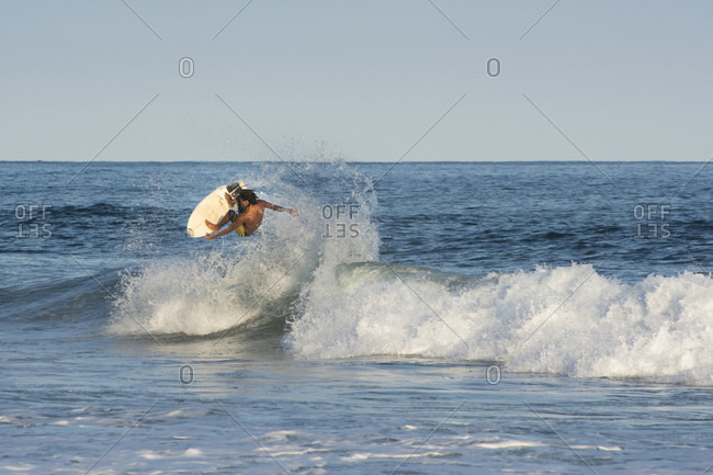 Agua Blanca, Oaxaca, Mexico - July 21, 2015: A young male surfer takes off of a wave and throws an aerial in Agua Blanca, Oaxaca, Mexico.