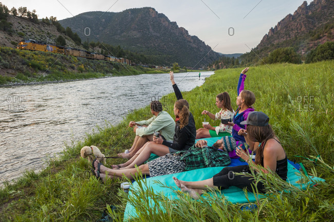 Kremmling, Colorado, USA - August 29, 2015: Boaters wave at a passing freight train while eating dinner by the Upper Colorado River at the Benches Campground near Kremmling, Colorado.