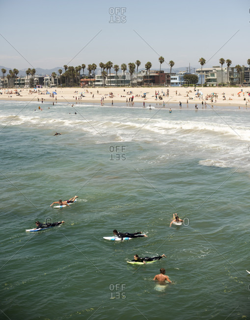 Venice, CA, USA - July 6, 2014: Surfers paddle out beyond the break while others relax in the sand on a sunny July 4, 2014 in Venice, Calif.