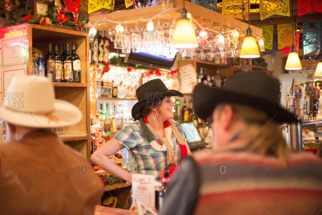 Santa Fe, NM, USA - December 21, 2013: A bartender chats with patrons at the Cowgirl BBQ restaurant in Santa Fe, New Mexico