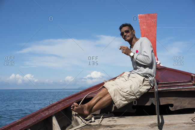 Koh Jum, Koh Jum, Thailand - May 3, 2015: A crewman of a longboat owned by the Koh Jum Resort shuttles guests from the resort to a passing ferry boat on its way to Krabi, Thailand