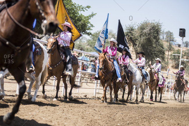 Woodlake, CA, USA - May 10, 2015: Cowgirls ride their horses during proceedings at the Woodlake Lions Rodeo rodeo in Woodlake, Calif.