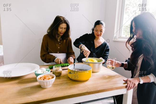 Women prepare meal together at table in kitchen
