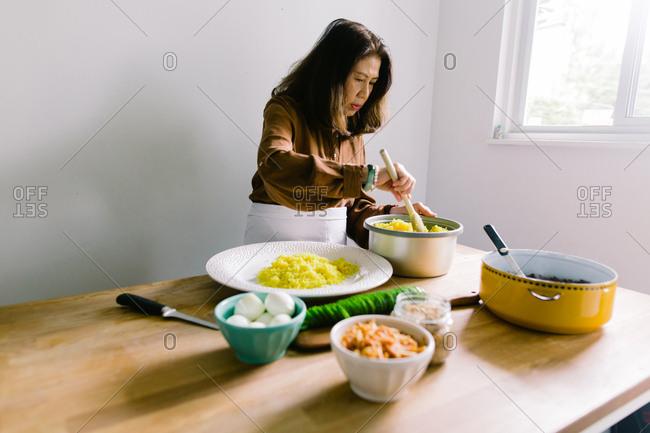 Senior woman scooping yellow rice onto round platter