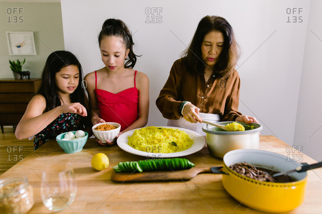 Granddaughters working with grandmother to prepare traditional Indonesian dish