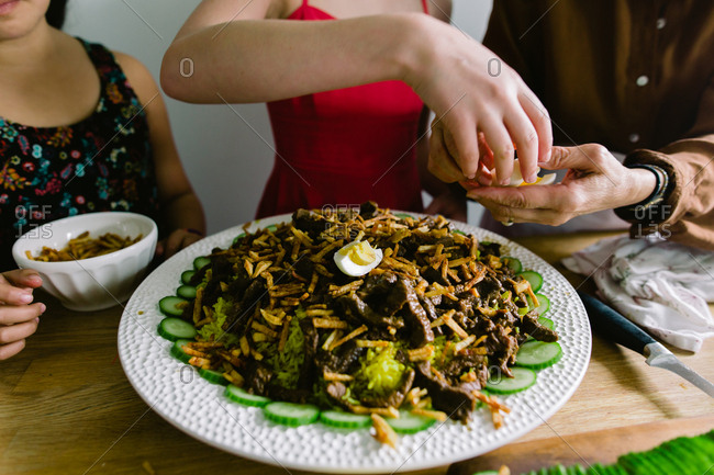 Girls help their grandmother prepare a traditional Indonesian dish