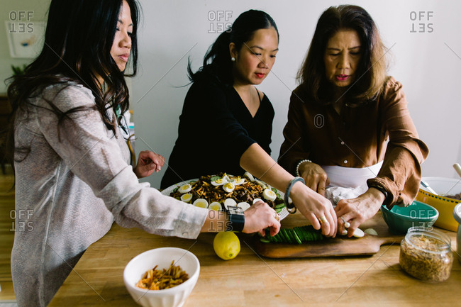 Woman and adult daughters prepare a traditional Indonesian meal