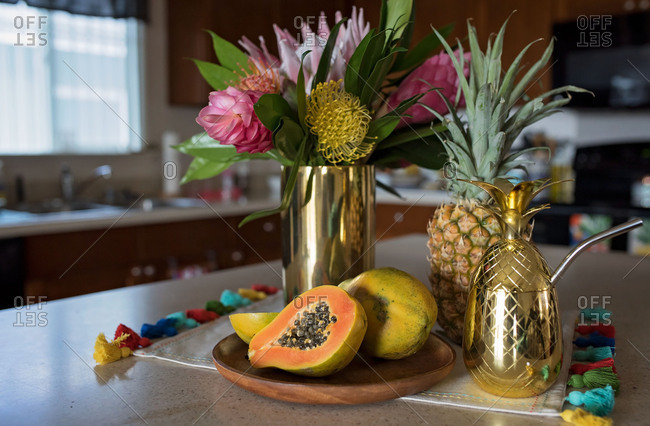 Tropical flowers on fruit on kitchen table
