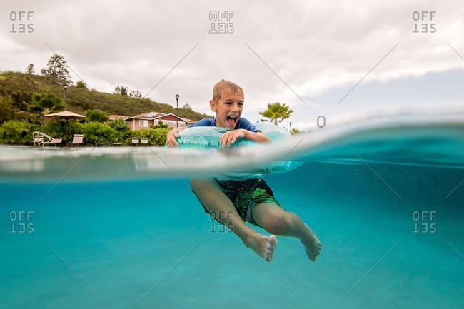 Waterline view of boy floating in a swim ring in blue water