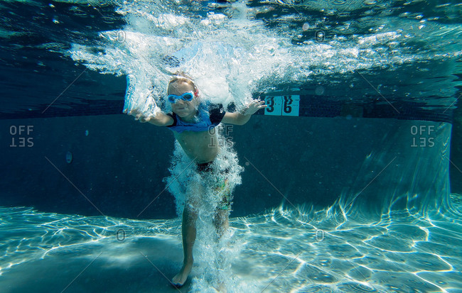 Underwater view of boy jumping in pool