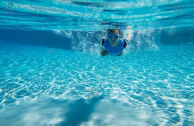 Boy swimming underwater in goggles