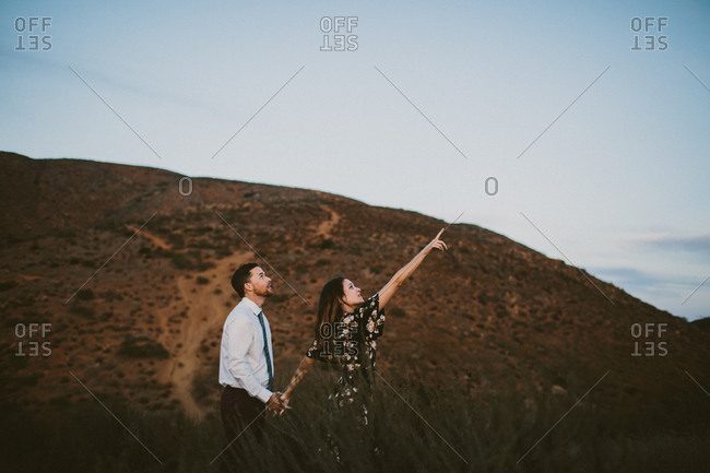 Man looks at something his partner is pointing at  in sky