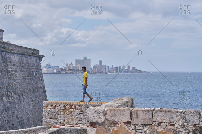 Havana, Cuba - March 7, 2017: Young man walking on the walls of Morro Castle with skyscrapers in the distance