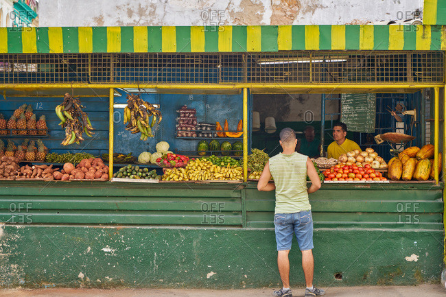 Havana, Cuba - March 8, 2017: Customer looking at fruits and vegetables at a produce stand