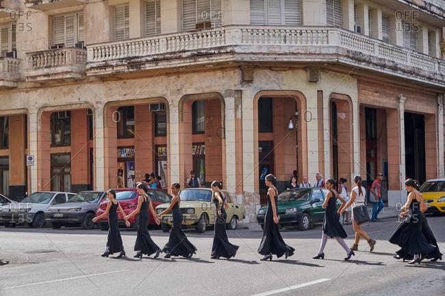 Havana, Cuba - March 8, 2017: Group of young dancers walking across a street