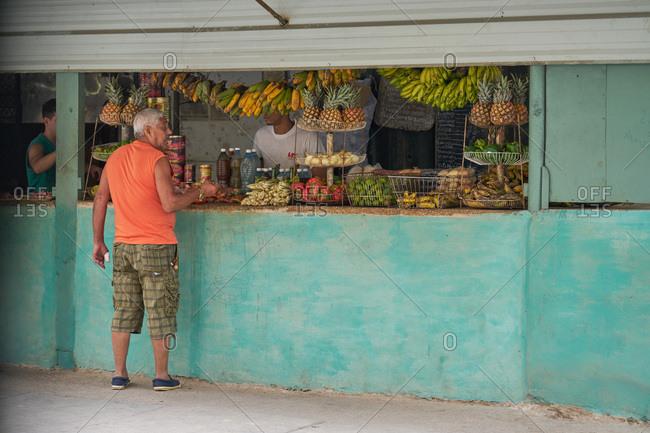 Havana, Cuba - March 9, 2017: Man buying fruit at a sidewalk produce stand