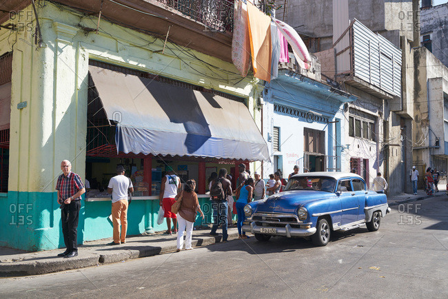 Havana, Cuba - March 10, 2017: People lining up on a street corner at an open-air cafe