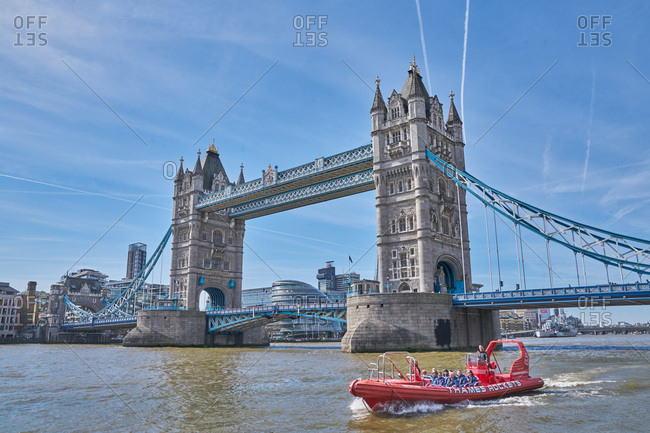 London, United Kingdom - March 26, 2017: Boat crossing the River Thames beneath the Tower Bridge