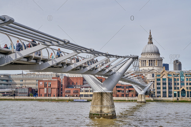 London, United Kingdom - March 26, 2017: Pedestrians crossing the Millennium Footbridge over the River Thames