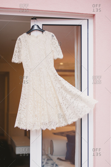 White lacy dress hanging on door
