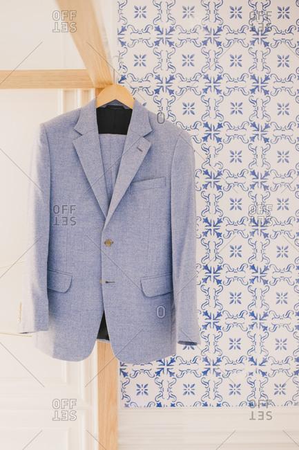 Men's suit hanging by tile