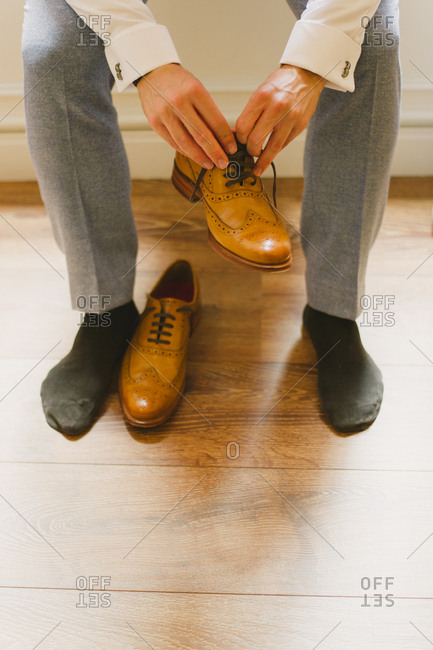 Groom putting on brown shoes