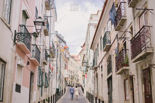 Lisbon, Portugal - January4, 2017: Bride and groom walking in street