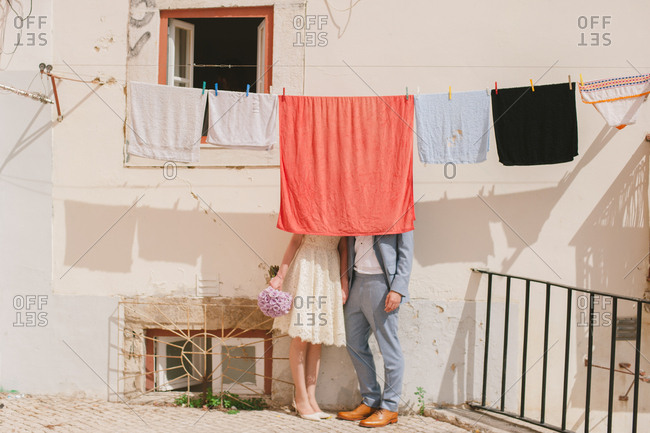 Bride and groom behind laundry
