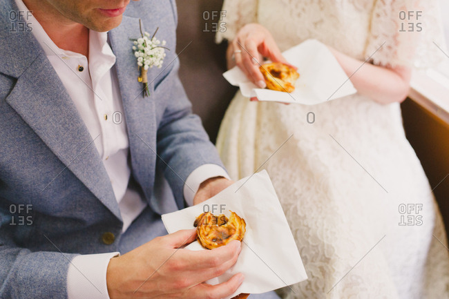 Bride and groom eating Portuguese tarts