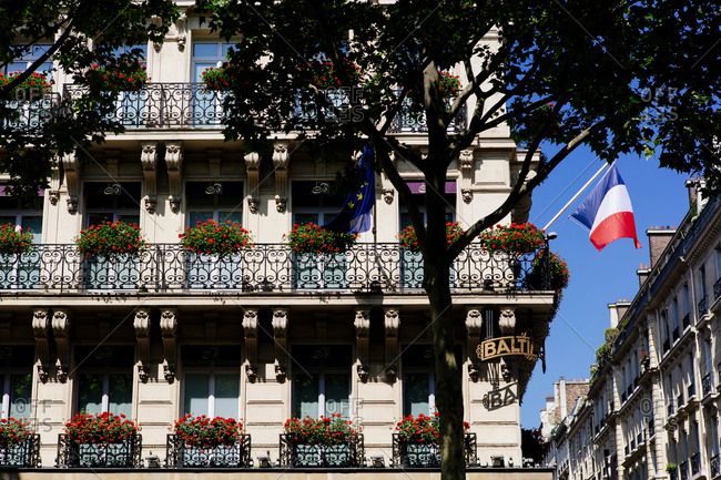 Building with balconies and red flower boxes in Paris, France