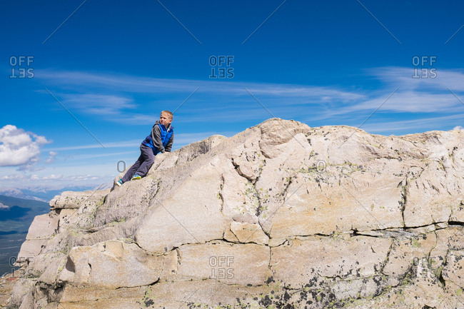 Boy climbing on mountain peak