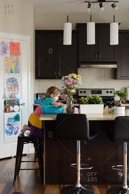 Girl playing at a kitchen counter