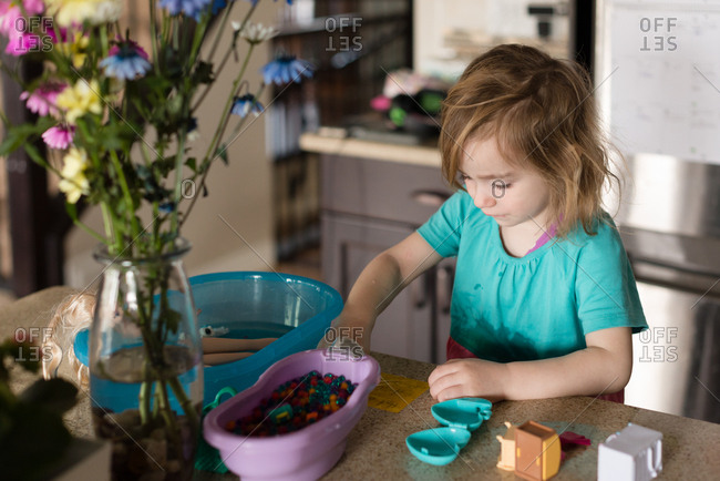 Girl playing at kitchen counter