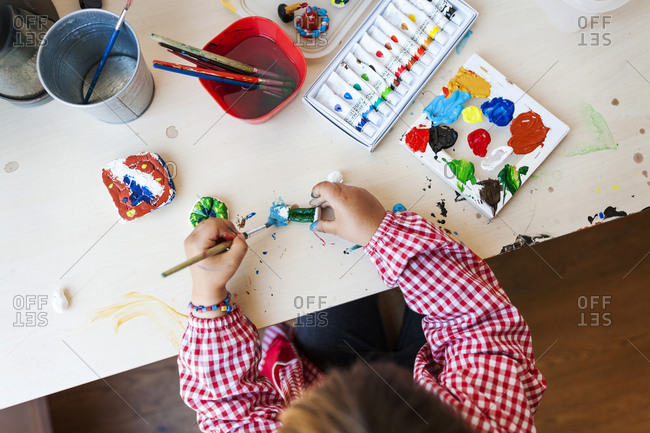 Child painting a clay figurine
