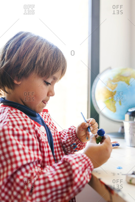 Child painting clay figurine
