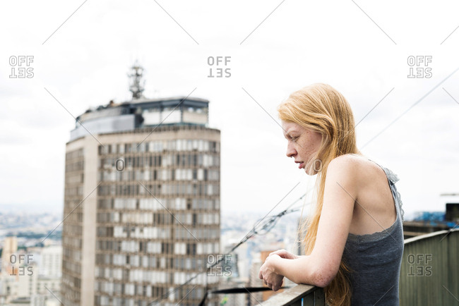 Woman looking over city roof