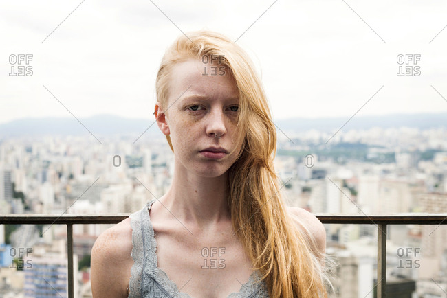 Woman with freckles over a city