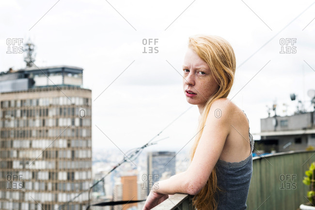 Woman with freckles on city roof